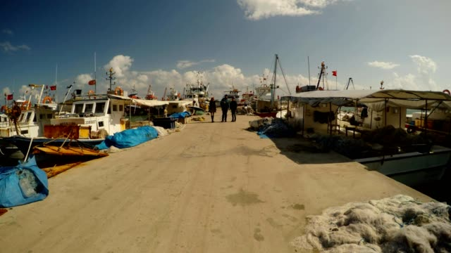 three-people-on-a-sea-fishing-Mediterranean-pier-with-boats-a-time-lapse-in-a-strong-wind-on-a-sunny-day