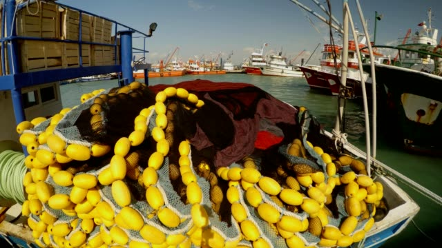 trawl-fishing-net-with-yellow-floats-lies-on-the-boat-ships-at-the-pier-in-the-distance