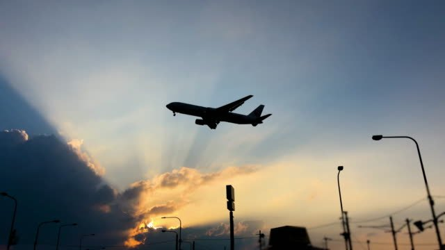 Airplane-flying-over-summer-sky-in-sunset
