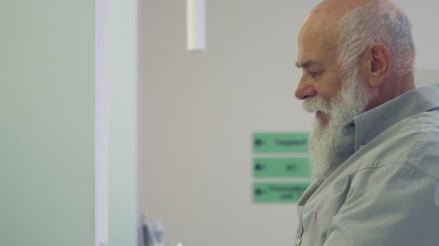 Senior-hombre-preguntar-cómo-fiil-el-formulario-del-hospital