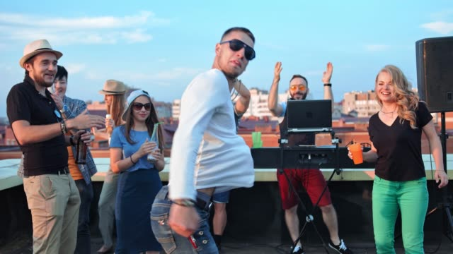 Male-hip-hop-dancer-in-sunglasses-modern-dancing-at-summer-rooftop-party