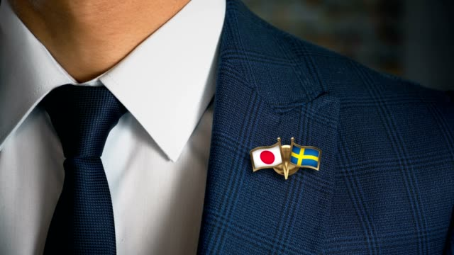 Businessman-Walking-Towards-Camera-With-Friend-Country-Flags-Pin-Japan---Sweden