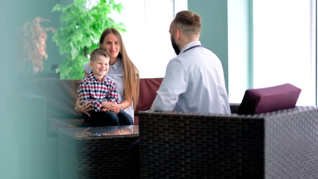 Mother-keeping-on-her-knees-little-son-sitting-in-chair-talking-with-doctor