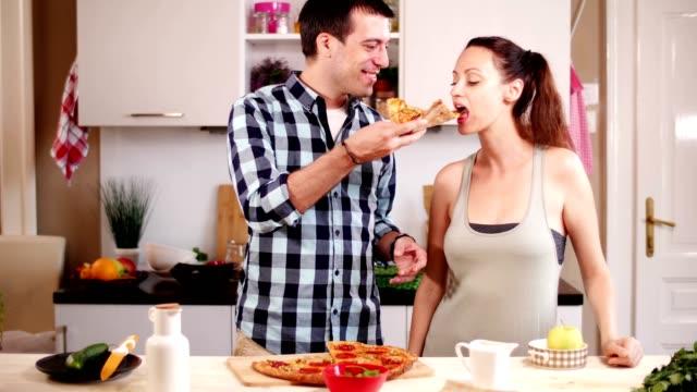 Boyfriend-feeding-pizza-to-Girlfriend-at-home
