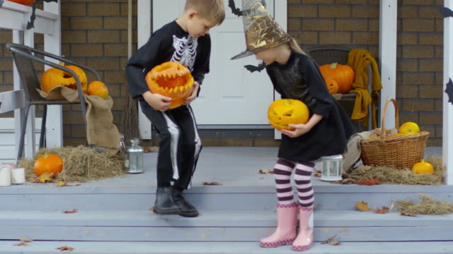 Kids-in-Halloween-Costumes-Playing-with-Jack-o-Lanterns