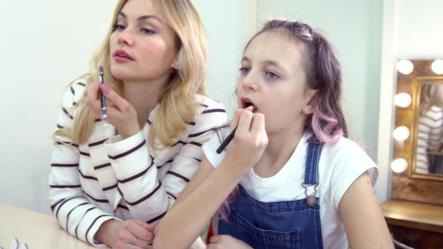 Mother-and-daughter-in-the-mirror-paint-their-lips-Reflection-