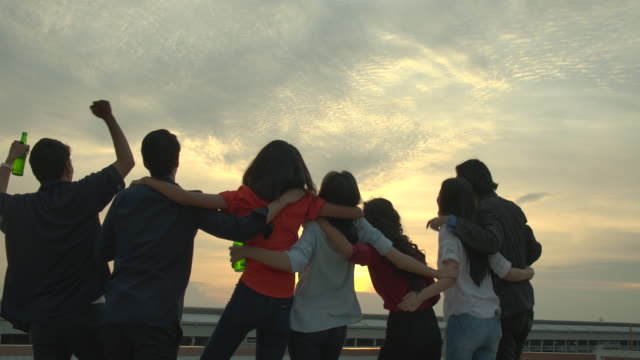 Group-of-young-friends-dancing-and-having-fun-celebrate-with-toast-and-clinking-raising-glasses-at-summer-rooftop-party-with-sunset-back-ground-Slow-Motion-