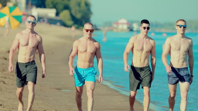 Portrait-of-beautiful-and-muscular-guys-walking-along-the-sandy-beach