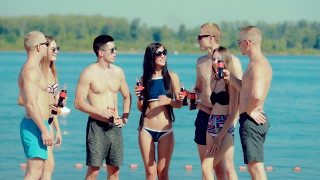 Jóvenes-amigos-felizes-en-un-semicírculo-y-comunican-en-la-playa-cerca-del-agua-con-botellas-de-refresco