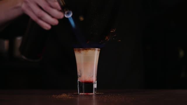 Der-Barkeeper-ist-einen-Cocktail-aus-Feuer-Hiroshima-cocktail-Das-Barkeeper-zündet-das-Feuerzeug-in-der-Leiste