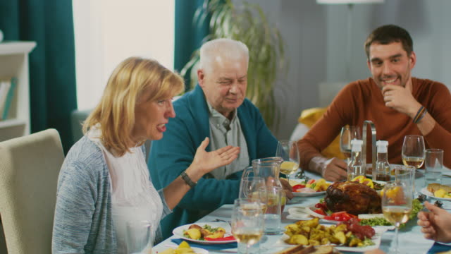Family-and-Friends-Gathering-at-the-Dining-Table-Senior-Couple-Talking-Joking-and-Eating-Old-and-Young-People-Having-Fun-Laughing-