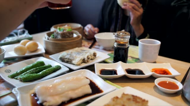 hand-pouring-condiment-sauces-for-group-during-gourmet-dim-sum-meal