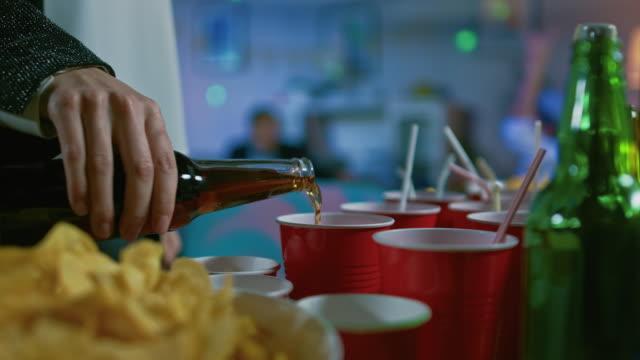 En-la-fiesta-salvaje:-persona-vierte-bebida-de-una-botella-de-Copa-roja-En-el-fondo-borroso-personas-bailando-