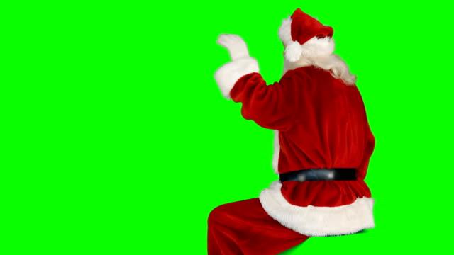 Vista-posterior-de-Papá-Noel-saludando-de-mano