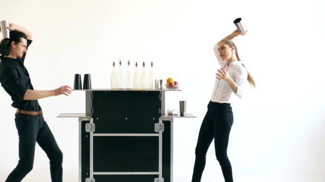 Professinal-bartender-man-and-woman-juggling-bottles-and-shaking-cocktail-at-mobile-bar-table-on-white-background