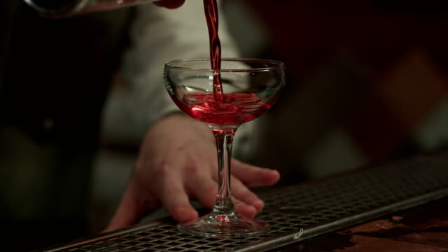 Barman-gießt-roten-Alkohol-und-bereitet-kosmopolitisch-ins-Champagnerglas