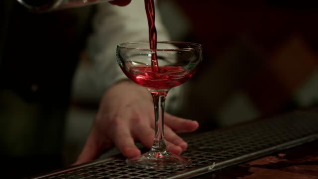 Barman-pouring-red-alcohol-preparing-cosmopolitan-into-champagne-glass