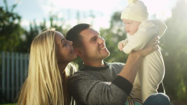 Joven-padre-y-la-madre-juegan-con-su-bebé-