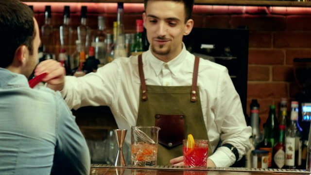 Barman-preparing-cocktail-for-a-client-and-waiting-for-his-reaction