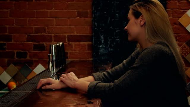 Joven-bonita-a-mujer-hablando-con-el-camarero-riendo-y-esperando-en-coctelería