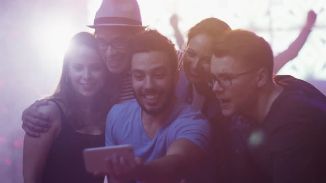 Group-of-Happy-Smiling-Friends-doing-Selfies-with-Mobile-Phone-on-Party-