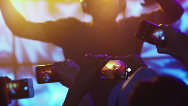 DJ-tocando-música-en-club-nocturno-la-gente-bailando-grabando-el-concierto-con-los-teléfonos-móviles-