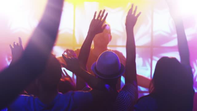 DJ-Playing-Music-in-Nightclub-People-Dancing-Having-Fun-and-Raising-Hands-