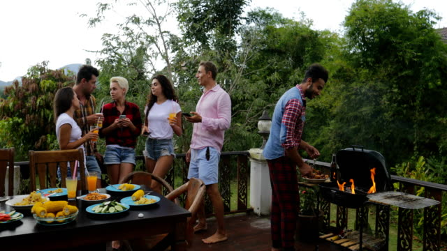 Young-People-Talking-Using-Cell-Smart-Phones-While-Latin-Man-Cooking-Barbecue-Friends-Group-Gathering-On-Summer-Terrace-Communication
