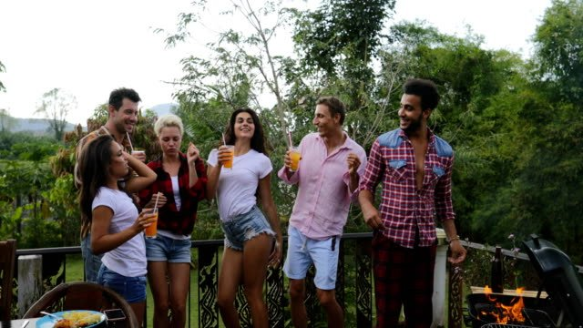 Young-People-Dancing-While-Latin-Man-Cooking-Barbecue-Friends-Group-Cheerful-Gathering-On-Summer-Terrace-Having-Party