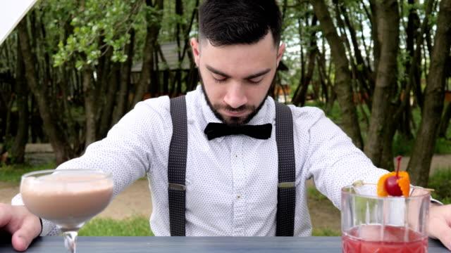 Porträt-Barkeeper-bei-der-Arbeit-hinter-der-bar-Barkeeper-close-up-Barkeeper-einreichen-Alkohol-farbige-gekühlte-Getränke-am-Tresen