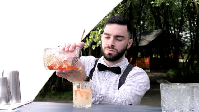 barman-pours-out-mixing-glass-into-prepared-wine-glass-with-liqueur-bar-worker-preparing-cocktail
