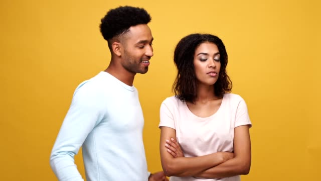 Confident-young-african-man-trying-to-ask-a-pretty-woman-out-for-a-date-isolated-over-yellow-background