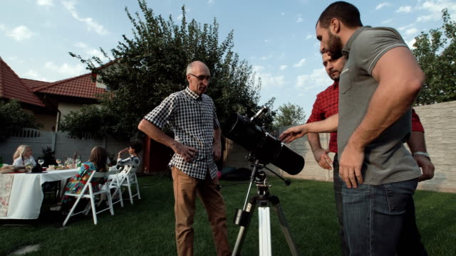 Men-watching-telescope-on-backyard