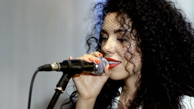 Beautiful-curly-brunette-with-veil-on-face-sings-in-microphone