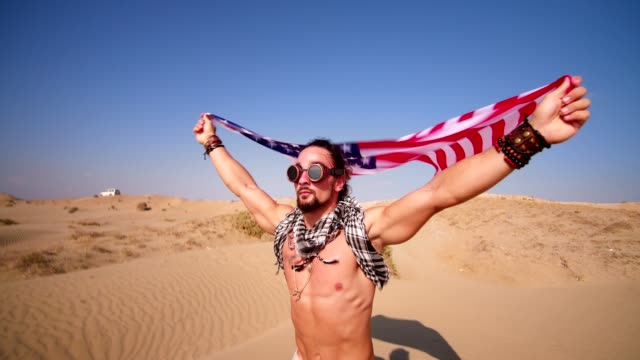Man-with-steampunk-goggles-and-american-flag-running-in-desert