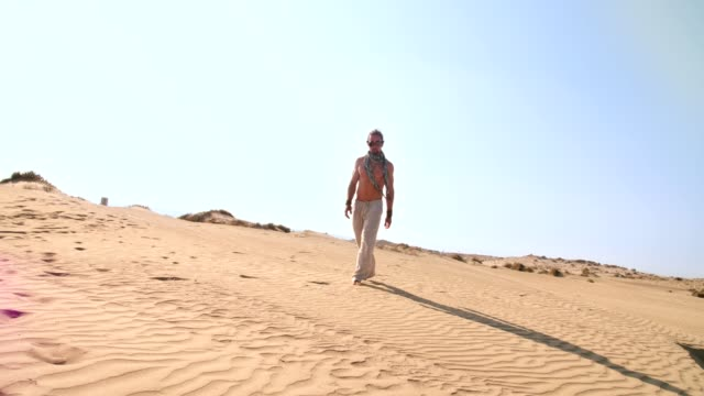 Young-man-with-steampunk-goggles-walking-alone-in-desert