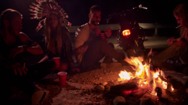 Young-rebel-motorcyclist-friends-drinking-and-smoking-around-campfire