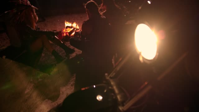 Group-of-motorcyclist-rebel-friends-sitting-and-drinking-around-bonfire