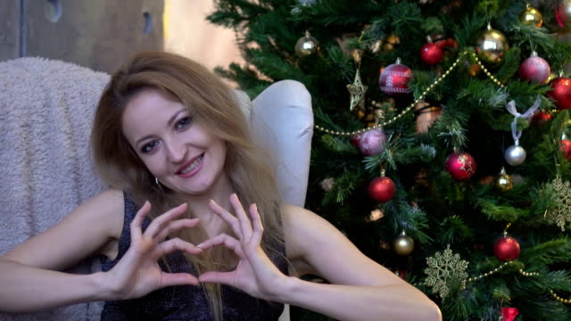 Pretty-young-girl-making-a-heart-with-her-hands-on-christmas-tree-background