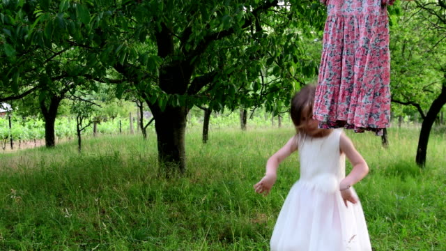 Danzas-de-una-linda-chica-en-el-jardín-natural-Niña-baila-y-salta-en-un-trampolín-pequeño-Niña-lleva-el-vestido-de-novia-blanco