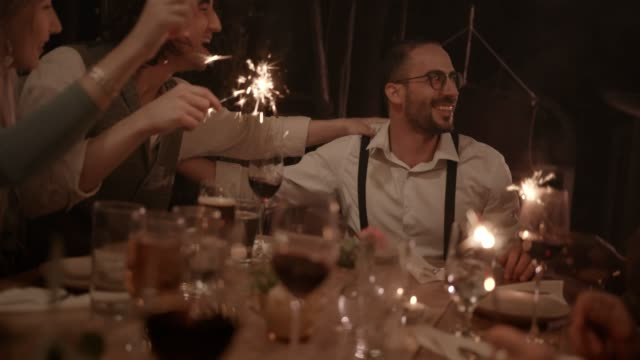Young-multi-ethnic-friends-celebrating-man-s-birthday-at-gourmet-dinner-party