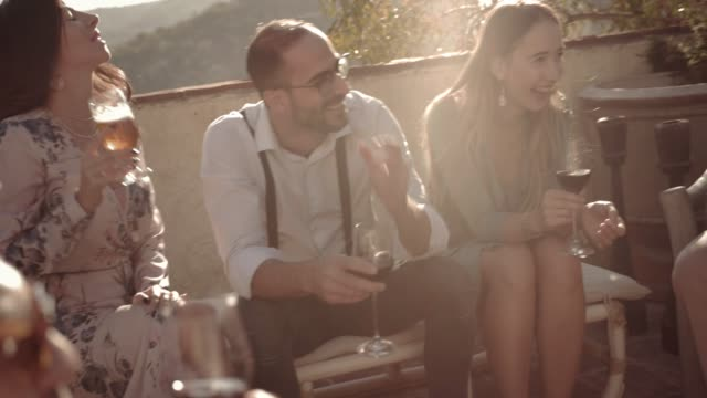 Elegant-multi-ethnic-friends-having-fun-and-drinking-wine-and-beer