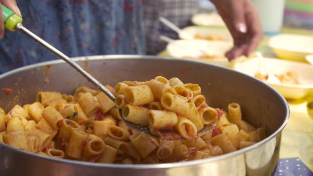 Young-happy-kids-preparing-eating-lunch-pasta-in-summer-camp-outside-on-sunny-day-in-park-serving-food-from-pot-pan-slow-motion