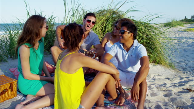 Multi-ethnic-friends-playing-guitar-and-enjoying-picnic