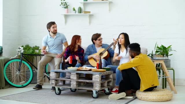 Amigos-felices-tienen-partido-y-cantar-juntos-mientras-su-amigo-tocando-la-guitarra-en-casa