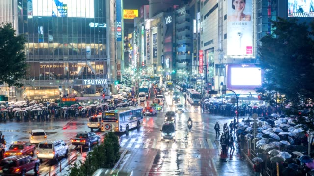 Night-timelapse-of-tourist-with-umbrella-walking-at-Shibuya-crossing-street-intersection-Shibuya-Tokyo-Japan-4K-time-lapse