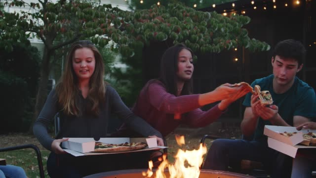 Teenage-friends-sit-round-a-firepit-eating-take-away-pizzas