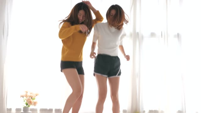 Asian-lesbian-couple-dancing-on-bed-Teenage-girls-are-dancing-with-fun-Fun-activity-of-two-girls-in-the-bedroom-