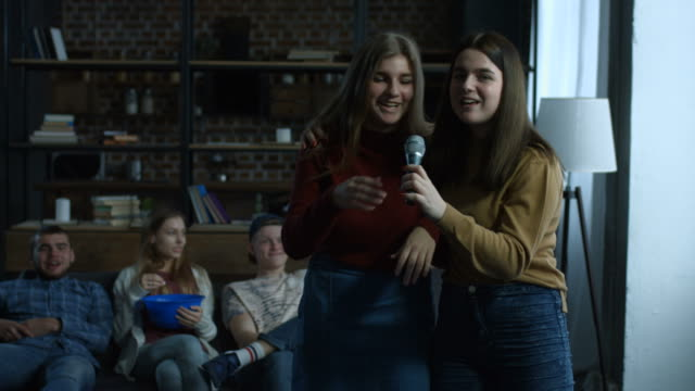Joyful-girls-singing-karaoke-in-domestic-room