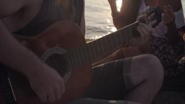 Man-Playing-Guitar-for-Friends-on-Beach